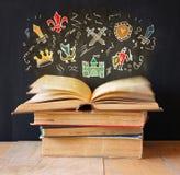 Foto da pilha de livros velhos o livro superior está aberto com grupo de infographics conceito da imaginação e da educação foto de stock royalty free