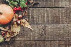 Foto da queda, abóbora bonita com folhas e bagas em rústico Foto de Stock