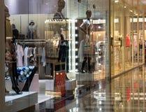 A foto da rua apresenta o estilo moderno da forma da roupa dos manequim da iluminação exterior dos objetos do vidro das lojas imagem de stock