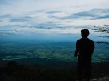Foto da silhueta do suporte do turista no penhasco na montanha de Khao Luang no parque nacional de Ramkhamhaeng foto de stock