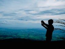 Foto da silhueta do suporte do turista no penhasco na montanha de Khao Luang no parque nacional de Ramkhamhaeng imagem de stock royalty free