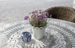 Foto da tabela acolhedor do café na rua da pedra de pavimentação na manhã ensolarada do verão com as flores bonitas na toalha de  imagem de stock