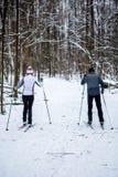 Foto dalla parte posteriore degli sport donna e dalla corsa con gli sci dell'uomo nella foresta di inverno Immagini Stock Libere da Diritti