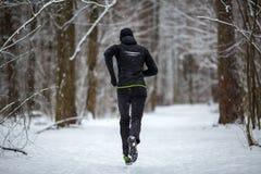 Foto dalla parte posteriore dell'atleta sul funzionamento nell'inverno fotografie stock libere da diritti