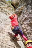 Foto dalla parte posteriore della donna sportiva in montagna rampicante rossa dell'uomo e del casco su Immagini Stock