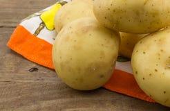 A foto das batatas fecha-se acima na madeira Imagem de Stock
