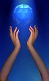 Foto das mãos de Womans que alcangam para a jóia que flutua no céu foto de stock royalty free