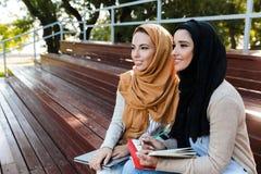 Foto das meninas islâmicas felizes que vestem os headscarfs que sentam-se no banco no parque fotos de stock royalty free