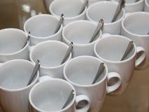 Foto, das nah zusammen diagonale Reihen 13 weiße Porzellanbecher mit Edelstahllöffeln steht Stockfoto