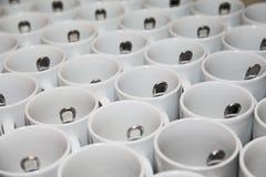 Foto, das nah zusammen diagonale Reihen 29 weiße Porzellanbecher mit Edelstahllöffeln steht Stockfoto