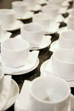 Foto, das nah zusammen diagonale Reihen 16 weiße Porzellanbecher steht Stockfotos