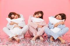 Foto das roupas vestindo sonolentos do lazer das mulheres 20s que guardam o comprimido Imagens de Stock Royalty Free