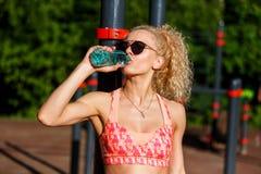 Foto de óculos de sol vestindo da mulher dos esportes com a garrafa da água perto da barra horizontal no parque Imagens de Stock