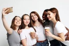 Foto de cinco meninas multi-?tnicos que riem e que tomam o selfie imagem de stock royalty free