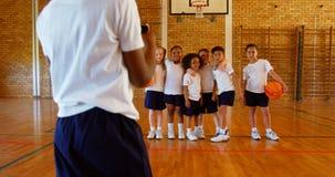 Foto de clique da estudante com telefone celular de seus amigos no campo de básquete na escola 4k video estoque