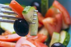 Foto de color de las verduras de ensalada en la bifurcación de la placa con el tomate y el pepino verdes olivas fotografía de archivo