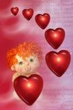 Foto de corazones flotantes rojos y pequeña muñeca del Cupid con verde Imagen de archivo libre de regalías