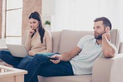 Foto de dos personas en amor que pasan su tiempo libre por separado Foto de archivo libre de regalías