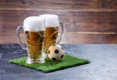 Foto de dos vidrios de la cerveza, balón de fútbol en hierba verde Fotografía de archivo