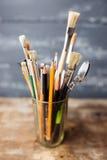 Foto de escovas de pintura em um vidro que está na tabela de madeira velha, Foto de Stock Royalty Free