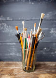 Foto de escovas de pintura em um vidro que está na tabela de madeira velha, Fotos de Stock Royalty Free