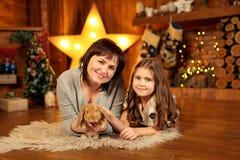 Foto de família da mãe e da filha que colocam no assoalho na chaminé com coelho bonito Decoração do Natal fotos de stock
