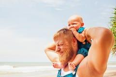 Foto de família engraçada O filho do bebê senta-se em ombros do pai foto de stock