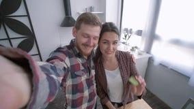 Foto de família na cozinha, fêmea alegre com a foto masculina do selfie da tomada no smartphone ao cozinhar a salada vegetal sobr filme