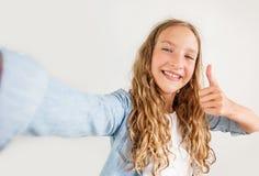 Foto de fatura adolescente de sorriso do selfie no smartphone sobre a menina bonito do fundo branco imagens de stock