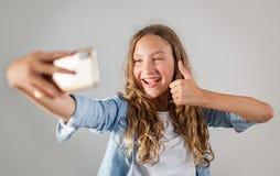 Foto de fatura adolescente de sorriso do selfie no smartphone sobre a menina bonito do fundo branco fotografia de stock