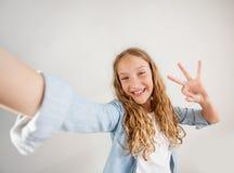 Foto de fatura adolescente de sorriso do selfie no smartphone sobre a menina bonito do fundo branco imagem de stock