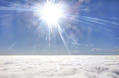 Foto de HDR de un ala del aeroplano contra el cielo azul con una capa de nubes debajo y el sol brillante del brigh adentro delant Imagen de archivo libre de regalías