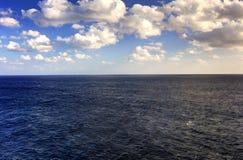 A foto de HDR do fim da tarde do mar que medem toda a maneira ao horizonte e o sol nebuloso azul do céu e o vermelho iluminam-se  foto de stock royalty free