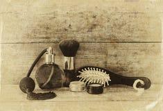 Foto de la botella de perfume del vintage al lado del cepillo para el pelo de madera viejo en la tabla de madera foto blanco y ne Fotos de archivo