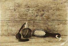 Foto de la botella de perfume del vintage al lado del cepillo para el pelo de madera viejo en la tabla de madera foto blanco y ne Fotografía de archivo libre de regalías