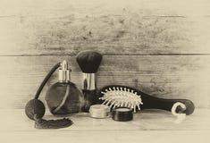 Foto de la botella de perfume del vintage al lado del cepillo para el pelo de madera viejo en la tabla de madera foto blanco y ne Fotos de archivo libres de regalías