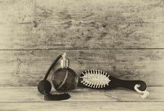 Foto de la botella de perfume del vintage al lado del cepillo para el pelo de madera viejo en la tabla de madera foto blanco y ne Foto de archivo