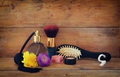 Foto de la botella de perfume del vintage al lado del cepillo para el pelo de madera viejo en la tabla de madera imagen filtrada  Imagen de archivo libre de regalías