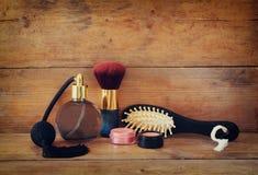 Foto de la botella de perfume del vintage al lado del cepillo para el pelo de madera viejo en la tabla de madera imagen filtrada  Foto de archivo