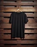 Foto de la camiseta negra que lleva a cabo encendido el fondo de madera Imagen de archivo libre de regalías