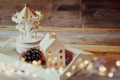 Foto de la casa, de los caballos del carrusel y de los conos decorativos del pino en fondo de madera Copie el espacio retro desco Imágenes de archivo libres de regalías