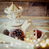 Foto de la casa, de los caballos del carrusel y de los conos decorativos del pino en fondo de madera Copie el espacio retro desco Imagenes de archivo