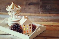 Foto de la casa, de los caballos del carrusel y de los conos decorativos del pino en fondo de madera Copie el espacio retro desco Imagen de archivo libre de regalías