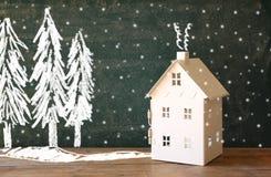 Foto de la casa del juguete delante de la pizarra con los dibujos del concepto del invierno Fotos de archivo libres de regalías