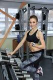 Foto de la chica joven atlética que hace un entrenamiento de la aptitud con pesas de gimnasia en el gimnasio foto de archivo libre de regalías