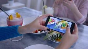 Foto de la comida, brazo de la muchacha que usa el teléfono móvil para las imágenes de la comida vegetariana durante el desayuno  almacen de metraje de vídeo