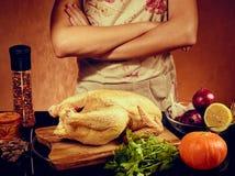 Foto de la comida del hombre irreconocible que cocina el pollo en el kitchencook en delantal en fondo anaranjado Imagenes de archivo