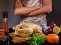 Foto de la comida del hombre irreconocible que cocina el pollo en el kitchencook en delantal en fondo gris Imagenes de archivo