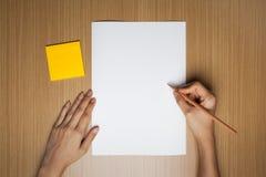 Foto de la escritura de la mano en el papel con el lápiz de madera Imágenes de archivo libres de regalías