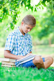 Foto de la escritura hermosa y de estudiar del adolescente con los libros en el th Fotos de archivo libres de regalías